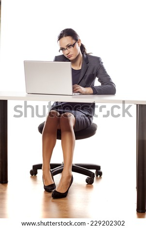 thinking business woman sitting at the table and working on her laptop - stock photo