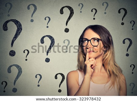 Thinking business woman with glasses looking up at many questions mark isolated on gray wall background - stock photo