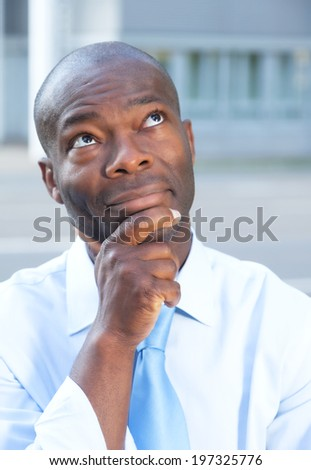 Thinking businessman from africa in front of his office - stock photo