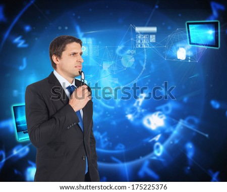 Thinking businessman holding glasses against blue background with letters