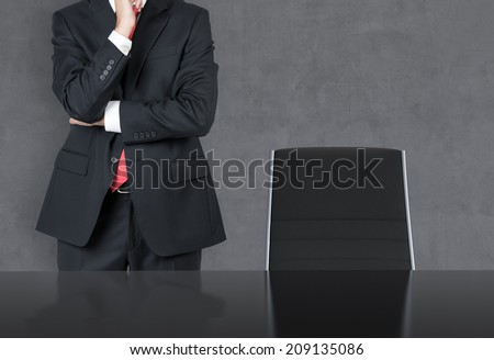 Thinking businessman in a suit in a dark Room with Chair and Table - stock photo