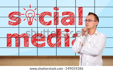 thinking businessman in office and  social media on plasma wall - stock photo