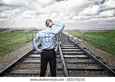 thinking businessman on train rail - stock photo