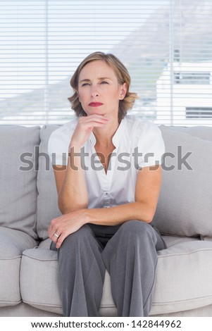 Thinking businesswoman sitting on couch in office