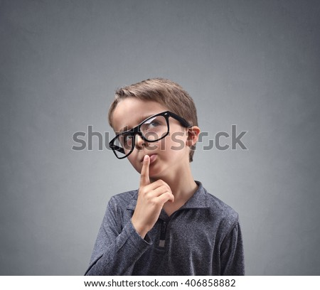Thinking child deep in thought concept for confusion, brainstorming, indecision, uncertainty and choice - stock photo