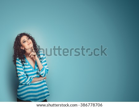 Thinking. Closeup portrait head shot happy mixed race daydreaming smiling cute confident latin female girl businesswoman isolated blue background wall. Positive human emotion feeling facial expression