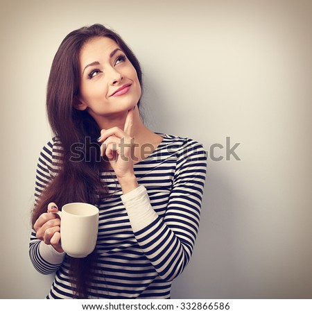 Thinking concerned young woman looking up with cup of coffee. Vintage portrait - stock photo