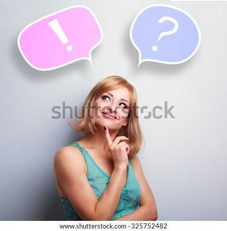 Thinking cute young woman with question and exclamation signs in bubbles above head on blue background - stock photo