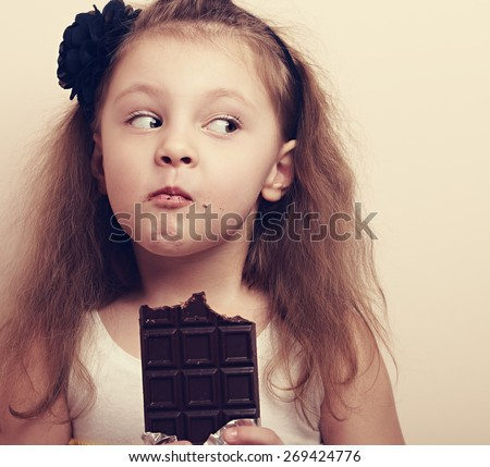Thinking expression kid girl eating chocolate and looking fun. Closeup instagram portrait - stock photo
