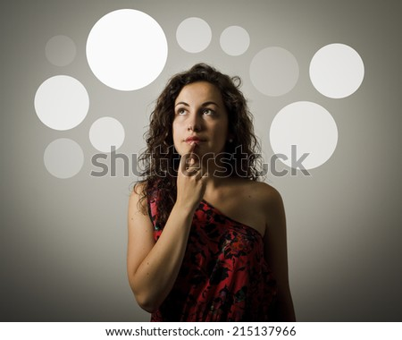 Thinking. Girl having an idea with gray bubbles over her head. Young woman doing something.  - stock photo