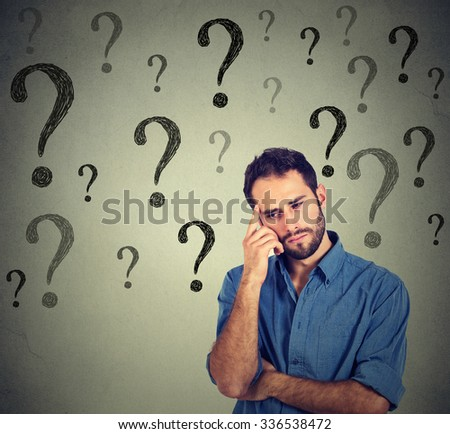 Thinking handsome young business man wondering looking down has many questions isolated on gray wall background with many question marks. Thinking guy   - stock photo