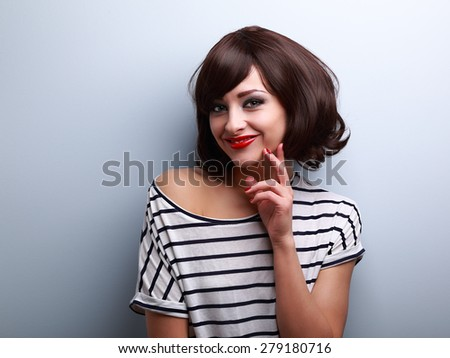 Thinking happy young woman with short hair looking on blue background with empty copy space - stock photo