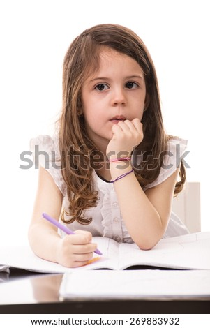 Thinking little girl drawing in kindergarten isolated on white background - stock photo