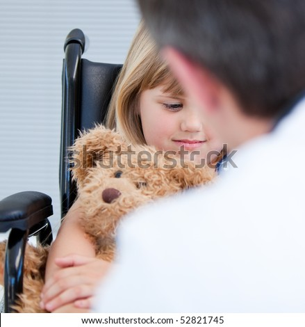 thinking little girl sitting on the wheelchair at the hospital