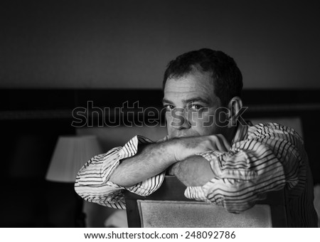 Thinking man sitting on a chair, leaning on his hands - stock photo