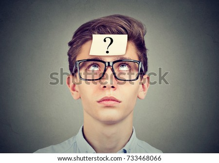 thinking man with question mark looking up on gray wall background