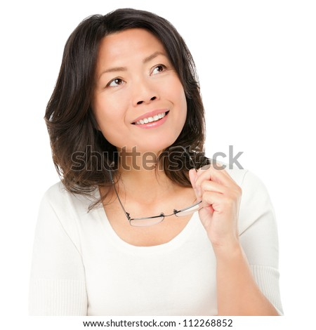 Thinking mature asian woman holding glasses eyewear looking up to the side at copy space. Asian Chinese mature woman isolated on white background in studio. - stock photo