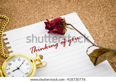 Thinking of you word in paper note with dry rose and pocket watch on desk.