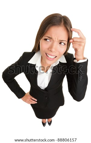 Thinking people. Business woman wondering funny looking to side pondering something while scratching head. High angle view of mixed race Caucasian /  Asian businesswoman isolated on white background. - stock photo