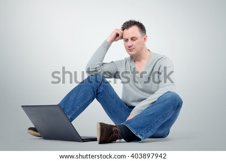 Thinking Programmer with laptop sitting on the floor - stock photo