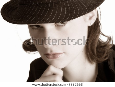 Thinking teen looking out from under the brim of her pinstriped fedora hat.  Isolated on white.