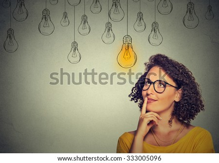 Thinking woman in glasses looking up with light idea bulb above head isolated on gray wall background - stock photo