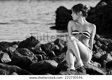 Thinking woman on the rocks near the sea black and white - stock photo