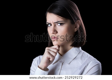 Thinking woman standing pensive contemplating looking skeptic.Thinking business woman expressing  anger,confusion and distrust.Young brunette looking curious,evaluating something - stock photo
