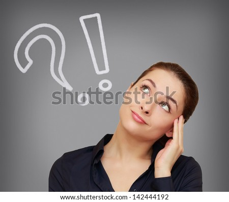 Thinking woman with question and exclamation mark looking on grey background