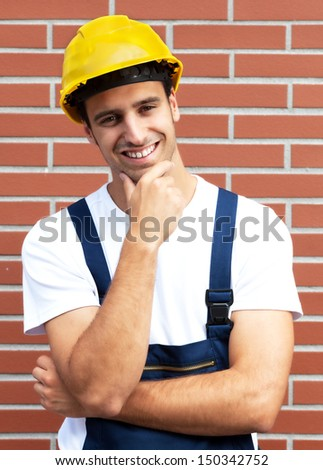 Thinking worker with a smile in front of a brick wall - stock photo