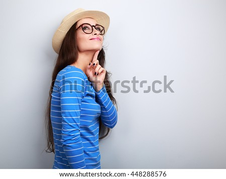 Thinking young happy woman in hat and glasses looking up on blue background