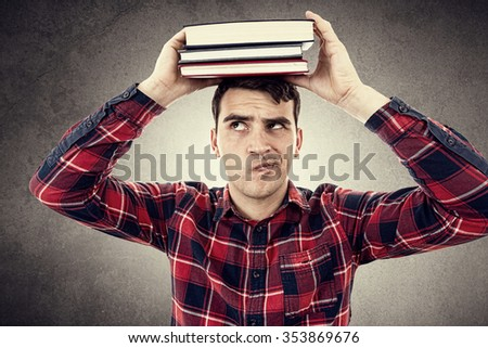 Thinking Young man student holding a  stack of books on head isolated over grey background.Curious young student man holding books on his head - stock photo