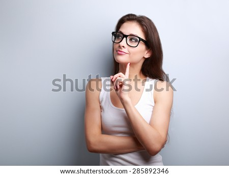 Thinking young woman in glasses looking on empty space background - stock photo