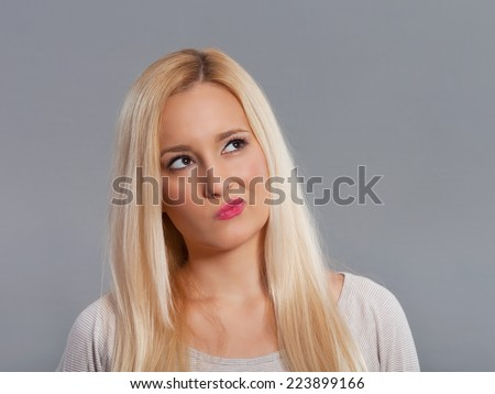 Thinking young woman looking up. Studio shot. - stock photo