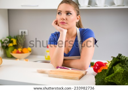 thinking young woman wondering what to cook in kitchen  - stock photo