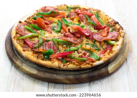 Thinly pepperoni pizza on wood table  - stock photo
