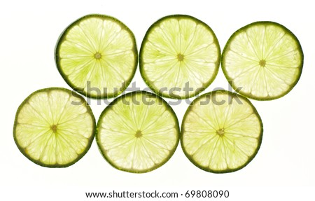 Thinly sliced pieces of lime lit from behind - stock photo