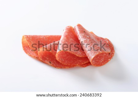 Thinly sliced salami infused with pieces of black truffles - stock photo