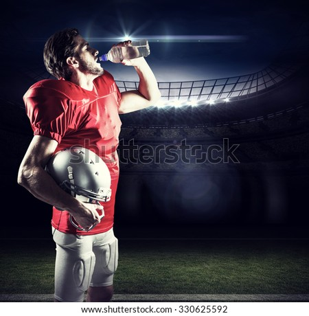 Thirsty American football player in red jersey drinking water against american football arena - stock photo