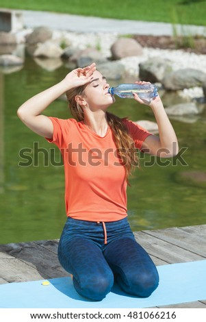 Thirsty attractive woman drinking water after outdoors workout