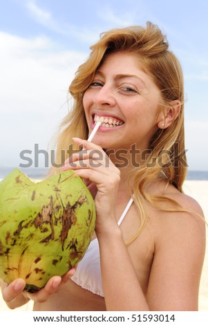 thirsty blond woman drinking coconut water on the beach