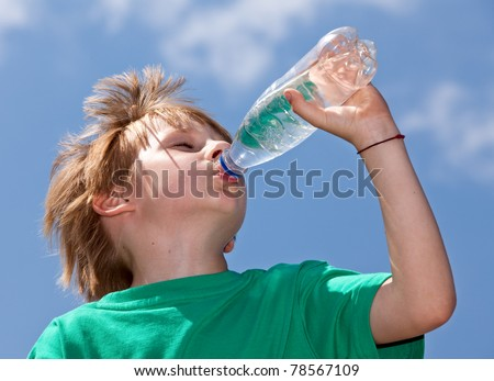 Thirsty boy drinking fresh water outdoors - stock photo