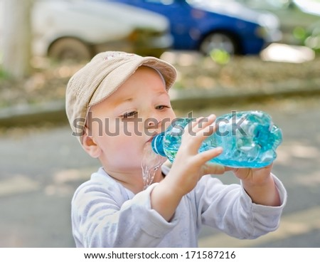 thirsty child drinking from a plastic bottle and spilling the water - stock photo
