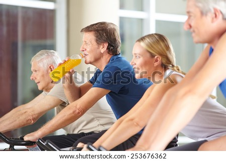 Thirsty man drinking orange juice in gym on spinning bike - stock photo