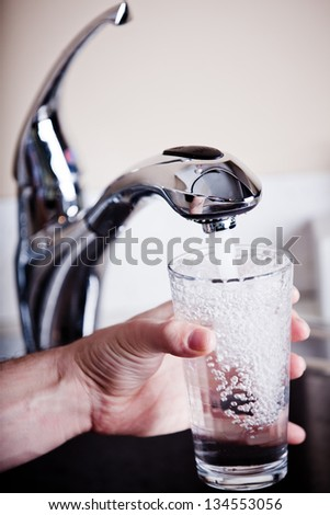 Thirsty man filling a glass of water - stock photo