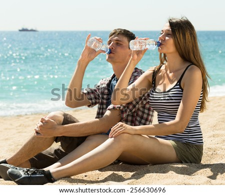 Thirsty young couple enjoying a refreshing drink of water at sunny day - stock photo