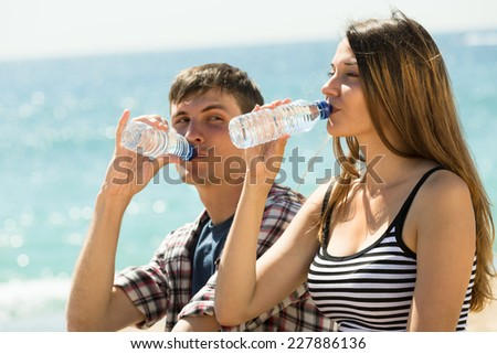 Thirsty young couple enjoying bottle of water at seashore in sunny day - stock photo
