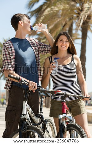 Thirsty young couple on bicycles taking a refreshing drink of water from bottle - stock photo