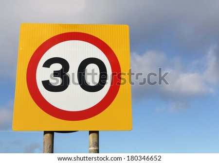 Thirty miles per hour speed limit sign against a partly cloudy sky.  - stock photo