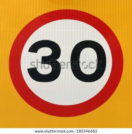 Thirty miles per hour speed limit sign with a yellow background. - stock photo